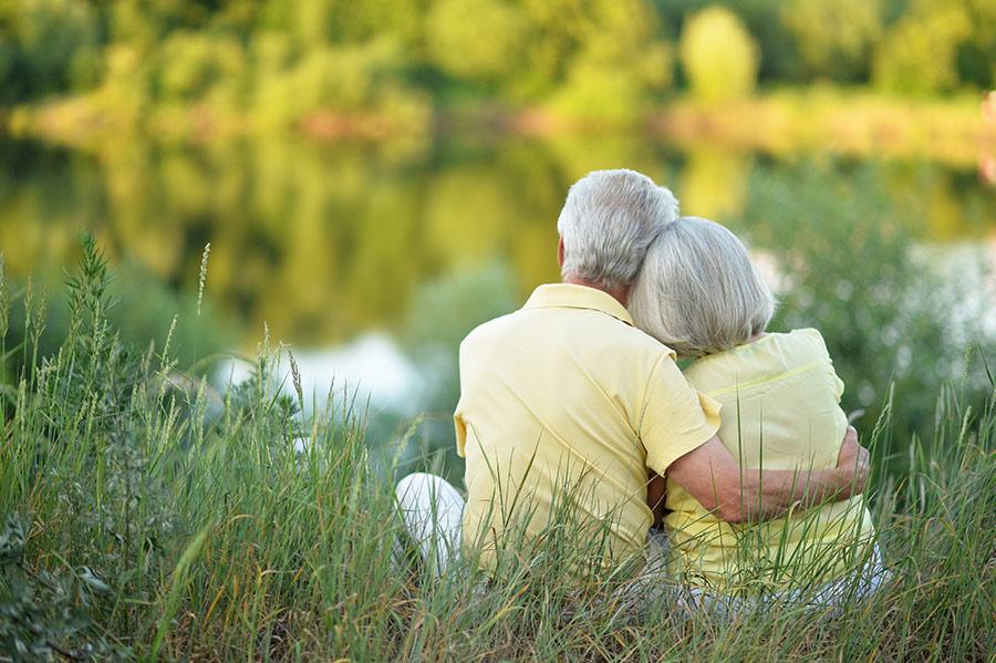 Een ouder stel, knuffelend aan de waterkant