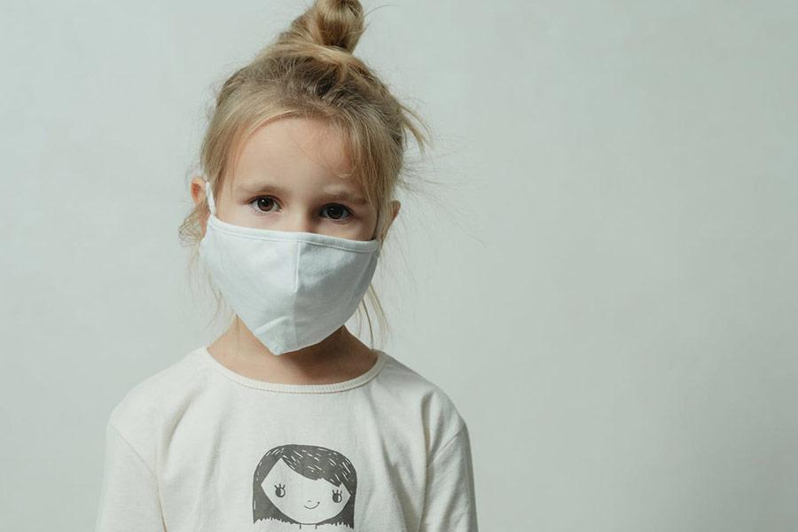 Een kind met een masker op kijkt verdrietig